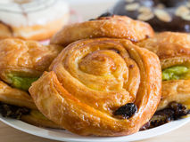 Delicious raisin danish pastry on wooden table. Delicious danish pastry on wooden table Royalty Free Stock Photography