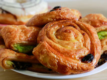 Delicious raisin danish pastry on wooden table. Delicious raisin danish pastry and donuts on wooden table Stock Image
