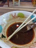 Delicious Rama soup. Half finished bowl of Rama soup from a restaurant in Thailand. Chop sticks and a spoon royalty free stock images