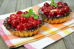 Delicious raspberries tarts on tablecloth on wooden table Royalty Free Stock Photography