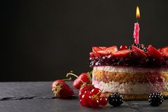 Delicious raspberry birthday cake. With fresh strawberry blueberry and blackberry on dark stone background with copy space Royalty Free Stock Image
