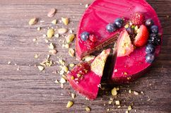 Delicious raspberry cake with fresh strawberries, raspberries, blueberry, currants and pistachios on wooden background.  Royalty Free Stock Images