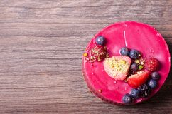 Delicious raspberry cake with fresh strawberries, raspberries, blueberry, currants and pistachios on wooden background. Free space for your text Royalty Free Stock Images