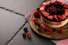 Delicious raspberry summer cake. With fresh strawberry blueberry and blackberry on dark stone background with copy space Stock Image
