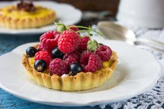 Delicious Raspberry tartlets with vanilla cream on blue wooden background. Top view. NDelicious Raspberry tartlets with vanilla cream on blue wooden background Royalty Free Stock Images