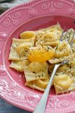 Delicious ravioli with parmesan and egg yolk. Homemade ravioli with egg yolk and black pepper in plate on white wooden table, selective focus Stock Photos