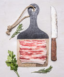 Delicious raw bacon on a cutting board with herbs and knife  wooden rustic background top view close up Royalty Free Stock Photo