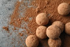 Delicious raw chocolate truffles on grey background, top view. With space for text stock images