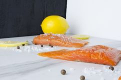 Delicious raw piece of salmon with lemon,peper and seasalt in three-dimensional space stock photo