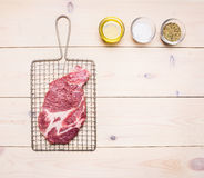 Delicious raw pork steak on the grill for grilling, there are a number of spices and oil, place text,frame on wooden rustic ba Stock Photos