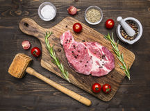 Delicious raw pork steak with rosemary and cherry tomatoes,  posted on a cutting board with spices and  hammer for meat  top view Stock Photography