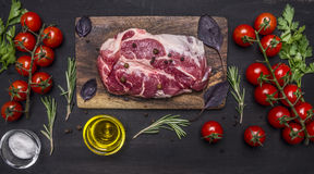 Delicious raw pork steak with spices and vegetables wooden rustic background top view close up Stock Photo