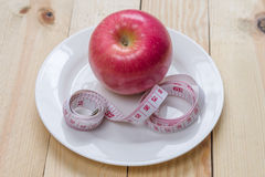 Delicious red apples and measured the meter on wooden background,Diet concept Royalty Free Stock Photo