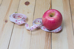 Delicious red apples and measured the meter on wooden background,Healthy food Stock Photos