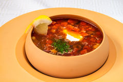 Delicious red soup with sour cream, herbs and lemon, in a dark yellow plate, on a white tablecloth. Horizontal frame royalty free stock image