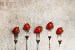 Delicious red strawberries punctured on forks. On a marble table stock images