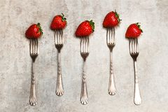 Delicious red strawberries punctured on forks. On a marble table royalty free stock images