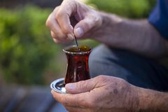 Delicious red Turkish tea with traditional pear shaped glass with a teaspoon in the man hand. Close-up of delicious red Turkish tea with traditional pear shaped Royalty Free Stock Photography