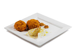 Delicious restaurant dessert  scoops of fried ice cream covered a crispy crust, served walnuts on square plate isolated Royalty Free Stock Images