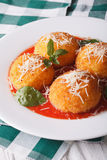 Delicious rice balls in tomato sauce on a plate close-up. vertic. Delicious arancini rice balls in tomato sauce on a plate close-up. vertical Royalty Free Stock Photography