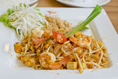 Delicious rice noodles with shrimp close-up on a plate. Thai Dis