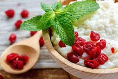 Delicious rice porridge with dried cherries and fresh mint. Rice porridge with dried cherries and fresh mint in a bowl closeup Stock Photo