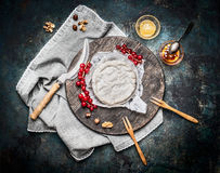 Delicious ripe camembert cheese on wooden cutting board with berries and sauce on rustic background, top view. Stock Image