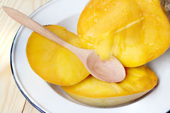 Delicious ripe mango fruit with wood spoon in whiter dish on wood background. Royalty Free Stock Photo