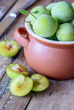 Delicious ripe plums in pot. On wooden table stock image