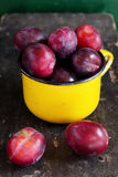 Delicious ripe plums in a yellow cup Royalty Free Stock Photo