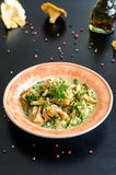 Delicious risotto with chanterelle mushrooms over rustic black background Stock Photography