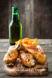 Delicious roast chicken drumsticks and chips,beer on cutting board and wooden table background background Royalty Free Stock Photography