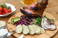 Delicious roast pork knuckle with rosemary, pepper, garlic, mustard and spices in the baking dish Stock Image