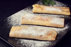 Delicious roast rolled pancakes with mint and powdered sugar on black plate stock photo