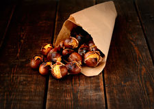 Delicious roasted chestnuts in a paper bag on a wooden background Stock Photos