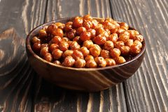 Roasted chickpeas in a bowl on a wooden background royalty free stock photography