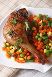 Delicious roasted duck leg with vegetables on a plate vertical Royalty Free Stock Photography