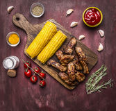 Delicious roasted lamb ribs with hot sauce, on a branch with tomatoes, roasted corn, spices, wooden rustic background top view Royalty Free Stock Images