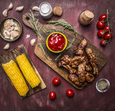 Delicious roasted lamb ribs with hot sauce and herbs on a cutting board with corn and vegetables wooden rustic background top v Stock Image