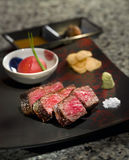 Delicious roasted Teppanyaki Japanese Yaeyama wagyu beef with wa. Sabi and toamtoes sauce on black platter deliciously Royalty Free Stock Images