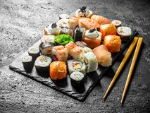 Delicious rolls, sushi and maki on a stone Board with chopsticks. On black rustic background stock photography