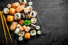 Delicious rolls, sushi and maki on a stone Board with chopsticks. On black rustic background stock photo