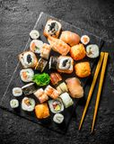 Delicious rolls, sushi and maki on a stone Board with chopsticks. On black rustic background stock photos