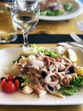 Delicious romantic dinner: salad with squids, octopus, olives and greens. royalty free stock images