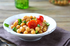 Delicious salad with boiled chickpeas and tomatoes on a bowl Stock Photos