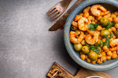 Delicious salad with Chickpeas, olives and shrimps in bowl and cutlery on gray concrete background, top view, border Royalty Free Stock Photography