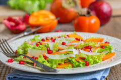 Delicious salad with persimmon. Healthy food. Royalty Free Stock Image