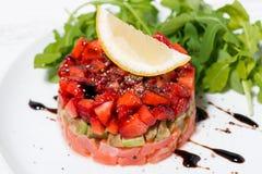 Delicious salad with salted fish, avocado and arugula, closeup. Horizontal stock image