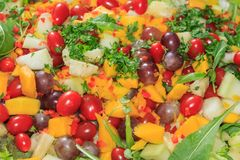 Delicious salad of vegetables and fruits. Lettuce, tomato, parsley, arugula, grape, mango, melon royalty free stock photos