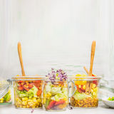 Delicious salads in glass jars with vegetables, lenses, corn and sprouts on light wooden background, side view, place for text Royalty Free Stock Images